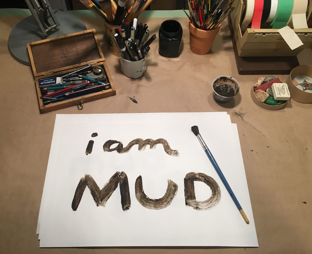 brown paint on paper reading i am MUD