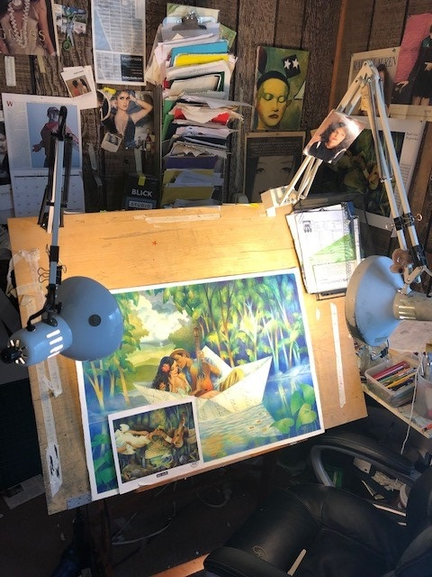 A photo of illustrator Raul Colon's workspace, featuring his painting easel with a work in progress: a scene of a man and woman in a boat.