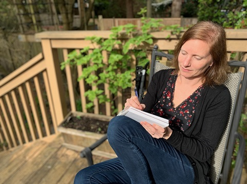 Author Tanya Lloyd Kyi writing on her outdoor deck.