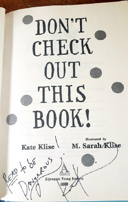 """The title page of Don't Check Out This Book, signed by the author Kate Klise with the message, """"Read to be dangerous!"""""""