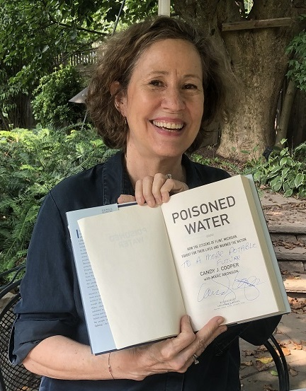 """Author Candy J. Cooper holding a copy of her book Poisoned Water, signed with the message, """"To a more potable future!"""""""