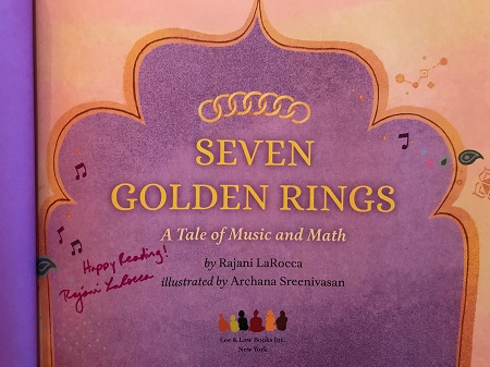 """The title page of Seven Golden Rings, signed by the author Rajani LaRocca with the message, """"Happy Reading!"""""""