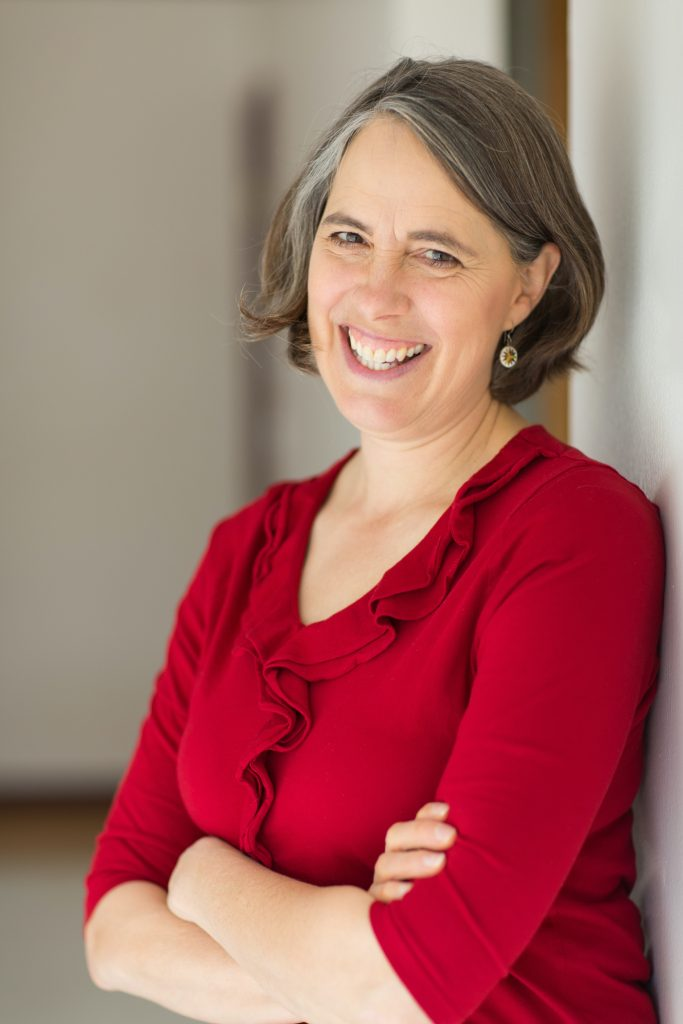 Image Description: Author Annette Bay Pimentel smiles leaning against a way wearing a red shirt.