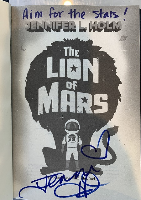 """The title page of The Lion of Mars, signed by the author, Jennifer L. Holm, with the message, """"Aim for the stars!"""""""