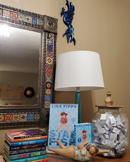 The space where author Lisa Fipps does virtual events. Pictured is a table with a mirror, a stack of books for young people, copies of Starfish and a figurine of a swimmer, and a jar filled with quotes on slips of paper.