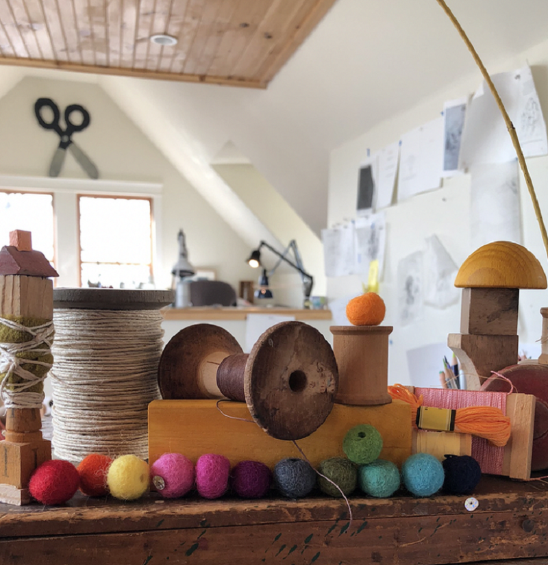 An interior image from Melissa Sweet's studio showing twine, brightly colored felt balls, wooden blocks, and other materials and inspiration for her artwork.