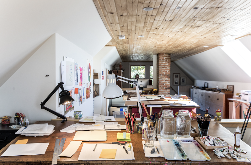 An interior image of Melissa Sweet's studio showing her worktable with paints and collage materials.