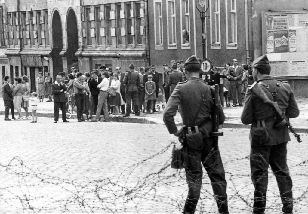 An archival image of teens from East and West Berlin facing off during the Cold War.