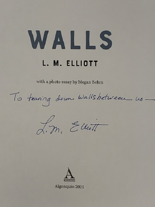 """The title page of Walls, signed by the author, L.M. Elliott, with the message, """"To tearing down the walls between us."""""""